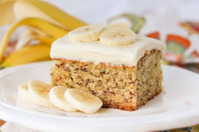 A slice of cake on a plate with bananas.