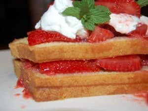 Layered Pound Cake topped with whipped cream and strawberries