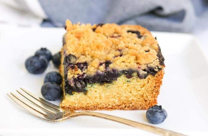 A slice of blueberry cake with crumb topping.