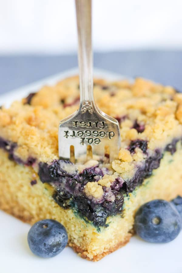 A fork sinking into a blueberry crumb cake.