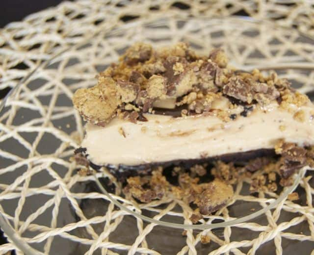 No-Bake Creamy Peanut Butter Pie - a crushed Oreo crust, with a thick, creamy, and delicious peanut butter filling drizzled with chocolate syrup, topped with crushed Reese's Peanut Butter Cups.