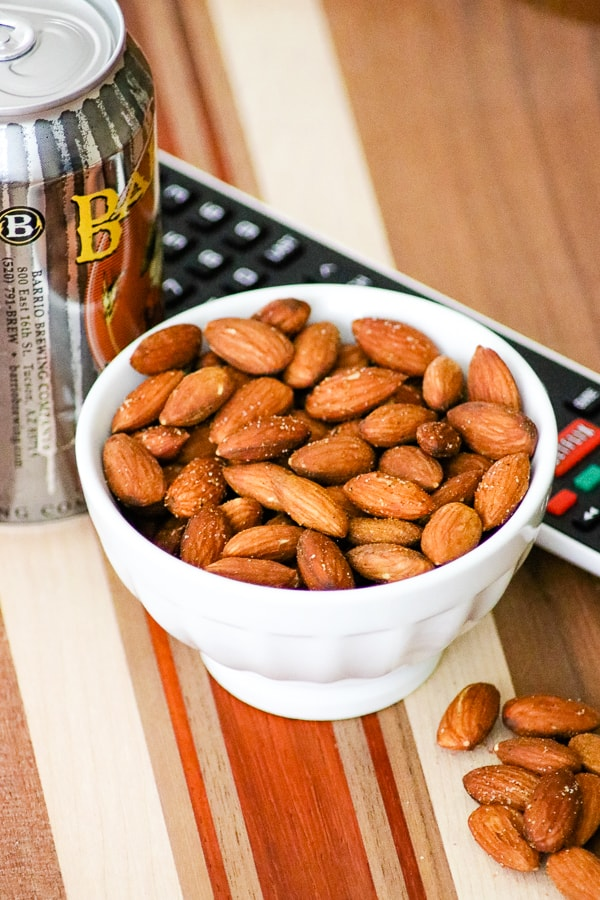 Bowl of Baked Spiced Almonds with a remote and can of beer.