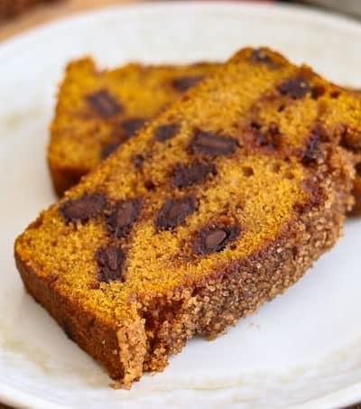 Two slices of Chocolate Chunk Pumpkin Bread with cinnamon sugar topping on a plate.
