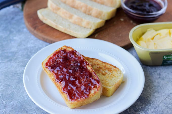 Slices of bread with jam on a plate.