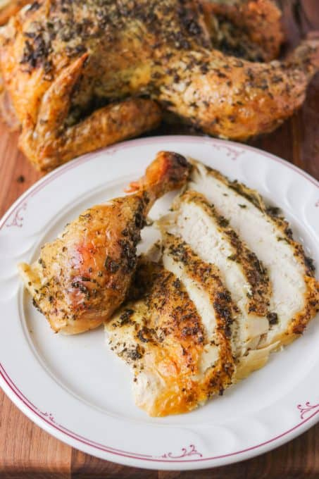 A drumstick and slices of chicken coated in herbs and lemon.