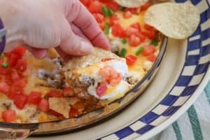 This Taco Dip is an easy game day dish to make, and fun to serve. The four layers of deliciousness are sure to please your hungry crowd. This dip of refried beans, taco seasoned ground beef, sour cream and Mexican cheese topped with diced tomato, jalapeño, and served with tortilla chips is a fan favorite at our house!