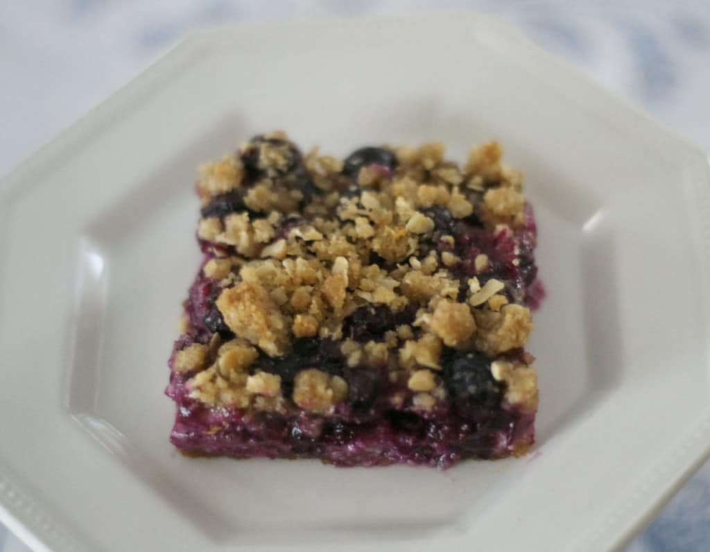 Blueberry Lemon Cheesecake Bars - lemony cheesecake bars covered in blueberries and a lemon streusel topping.