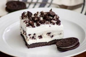 Oreo Pudding Dream Bars or Cookies and Cream Bars on a plate with an Oreo cookie.