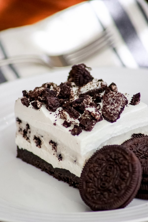 Oreo Pudding Dream Bars or Cookies and Cream Bars on a plate with some Oreo cookies.