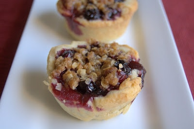 A bite-size pie filled with a fresh blueberry and cherry filling covered with a crumb topping.