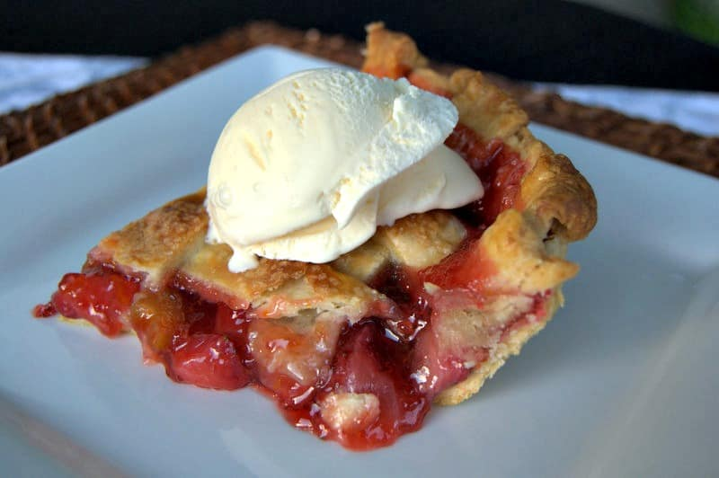 A lattice topped pie filled with a deliciously tart, yet sweet strawberry rhubarb filling accentuated with orange zest .