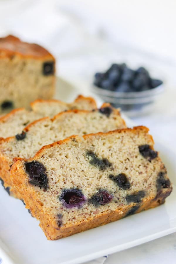 Slices of quick bread, blueberry banana bread on a plate with blueberries behind it.