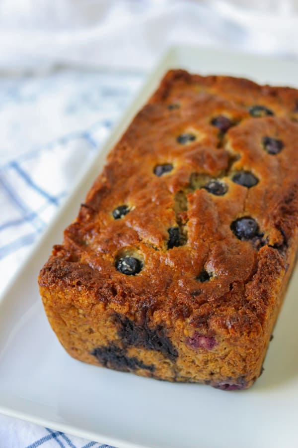 A loaf of banana bread with blueberries in it.