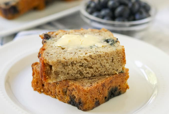 A buttered slice of quick bread with blueberries in the background.