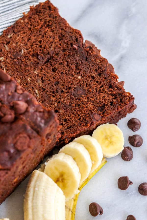 A slice of Double Chocolate Banana Bread next to a sliced banana and chocolate chips.