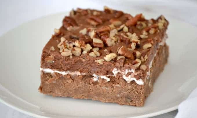 Mississippi Mud Cake is a rich chocolate cake with pecans and coconut, topped with a layer of marshmallow cream, chocolate frosting and more pecan pieces.