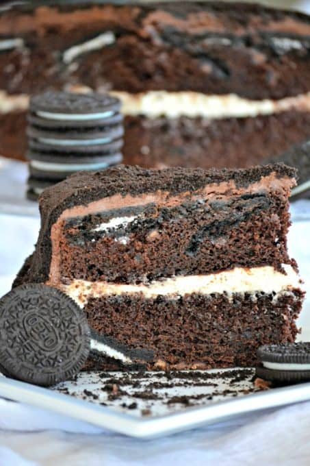 This Oreo Cake is a surprise-inside cake with chocolate layers, an Oreo filling, covered in chocolate buttercream and topped with Oreo cookie crumbs.