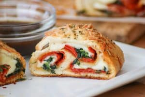 This Spinach Pepperoni Bread is pizza dough filled with spinach, pepperoni, and provolone. It makes a great weeknight dinner, is the perfect finger food for Game Day and is a recipe you'll be asked to bring again to that next potluck!