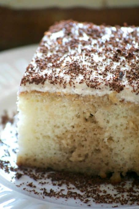 This Easy Tiramisu Poke Cake is a simple white cake drizzled with a sweetened coffee syrup, and topped with a whipped mascarpone vanilla frosting.
