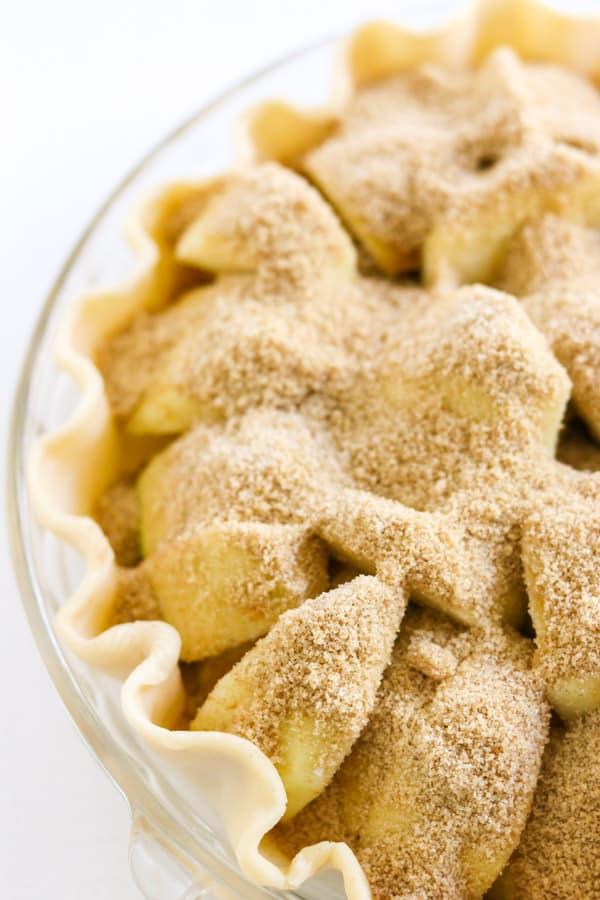 Cinnamon sugar on top of apples in a pie.