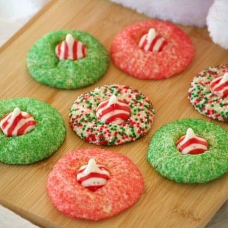 These Peppermint Blossom Cookies are a simple peppermint sugar cookie rolled in colored sugar and mulit-colored nonpareils with a Hershey's Peppermint Kiss.