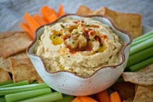 This Roasted Garlic Hummus is roasted cloves of garlic, tahini, lemon juice and spices. Served with pita chips or veggies, it's the perfect healthy treat.