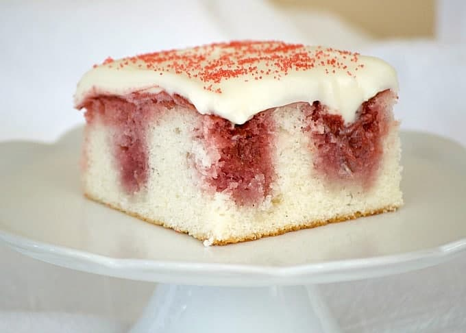 This Strawberry Poke Cake made from scratch with a white cake, strawberry sauce and cream cheese frosting is a perfect Valentine's Day or any day dessert.