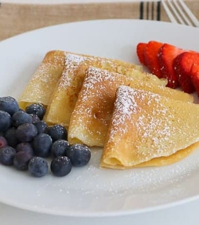 My family absolutely loves this Easy Crepe Recipe and yours will, too. Simply made with flour, eggs, milk and a little sugar, these thin French crepes or pancakes can be enjoyed a variety of ways. My favorite way to eat them is warmed with some pure maple syrup, but they're delicious with fillings, too!