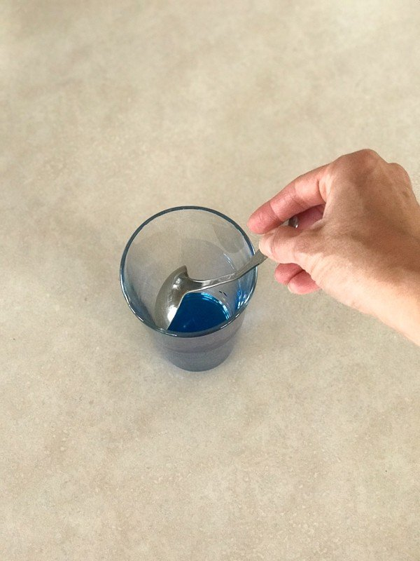 Holding a spoon against the glass to make a Blue Ocean drink recipe.