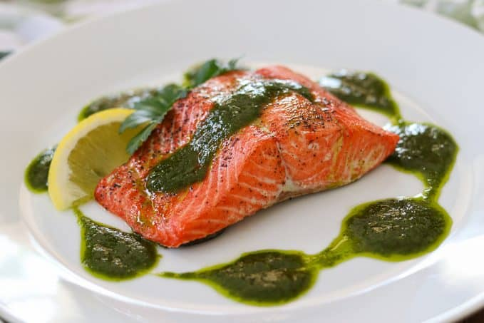 A salmon fillet topped with a chimichurri sauce.
