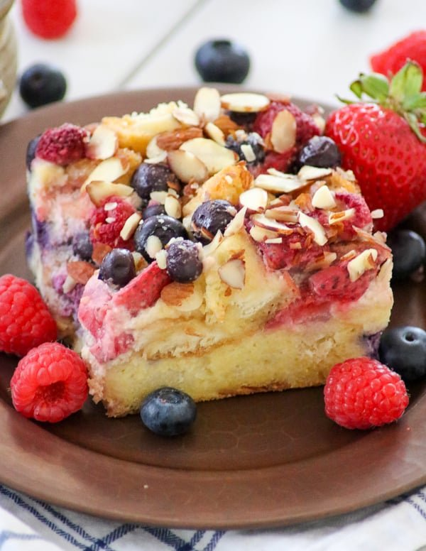 Almond Berry French Toast Casserole surrounded by fresh blueberries, raspberries and strawberries.