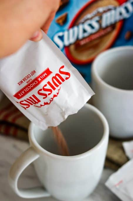 Emptying a packet of Swiss Miss Milk Chocolate Hot Cocoa into a mug.