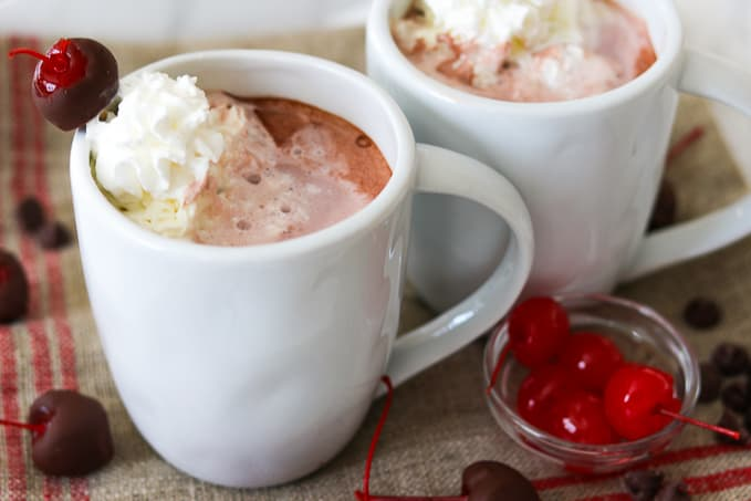 A mug of Chocolate Covered Cherry Hot Chocolate and cherries.