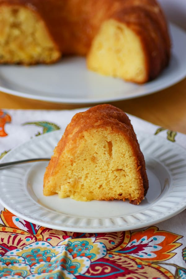 A slice of Pineapple Rum Cake on a plate with a fork.