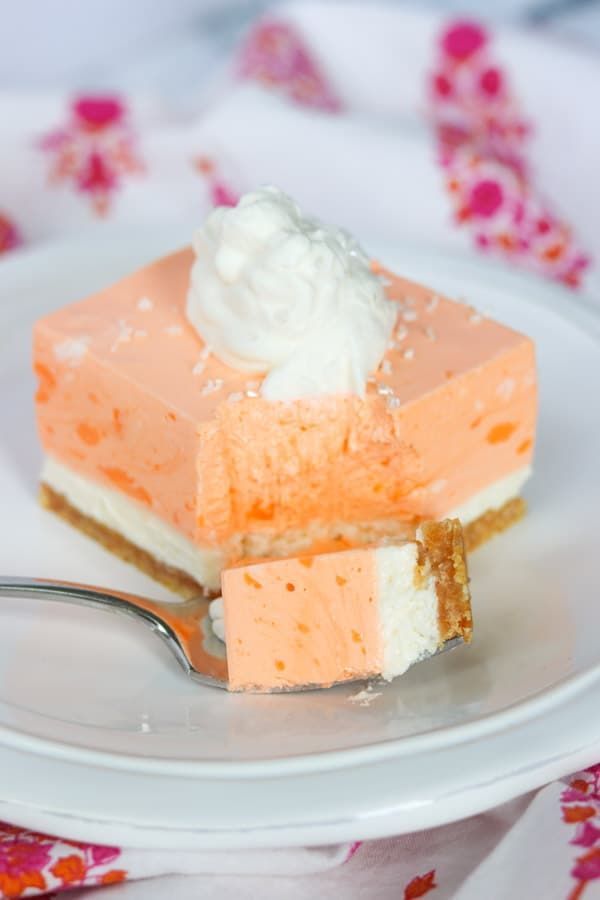 A bite of Orange Creamsicle Dream Bars on a plate.