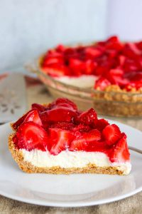 A slice of Strawberry Pretzel Pie with the pie in the background.