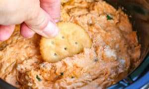 Ritz cracker dipping into the Slow Cooker Buffalo Chicken Dip.