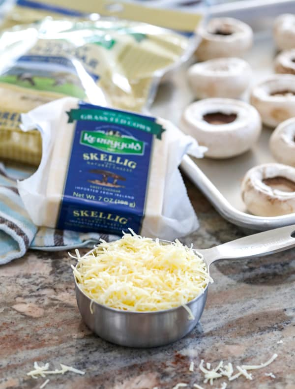 Grated Kerrygold Skellig cheese and Kerrygold Shredded Savory Cheddar for Cheesy Sausage Stuffed Mushrooms.