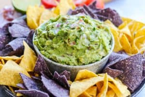 A bowlful of easy guacamole surrounded bu tortilla chips.