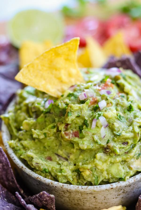 A tortilla chip in a bowl of easy homemade guacamole.