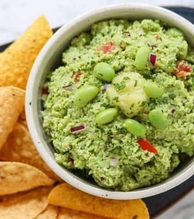 A bowl of guacamole with edamame and ginger surrounded by chips.