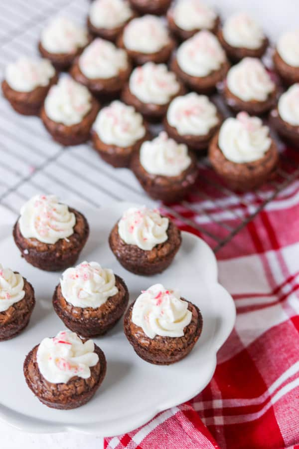 Frosted peppermint brownie bites with crushed candy canes on top.