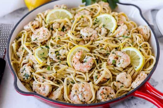 A skillet full of linguine with lemon, garlic, and shrimp.