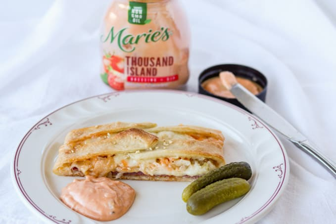 A plate with pickles, Marie's Thousand Island Dressing and a Reuben Braid slice.