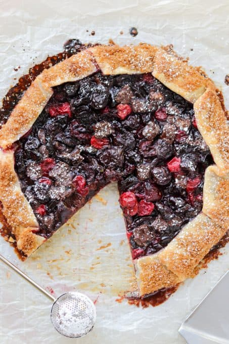 A piece removed from a galette with cherries and dark chocolate.