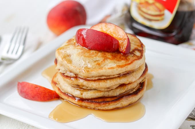 Cinnamon Pancakes topped with peaches and maple syrup.