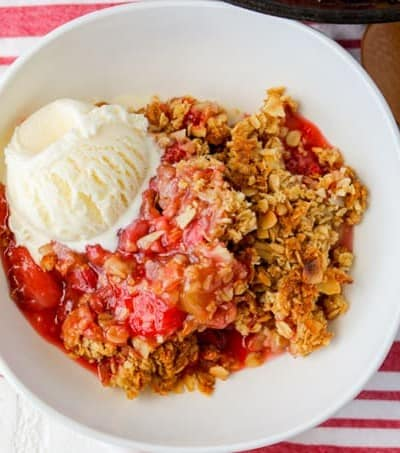A bowl of Skillet Strawberry Rhubarb Crisp with a scoop of ice cream.