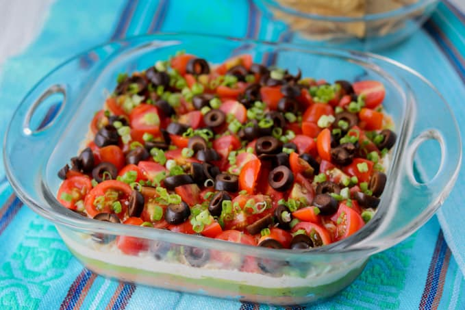 Layers of beans, guacamole, sour cream, tomatoes, olives, green onions and cheese.